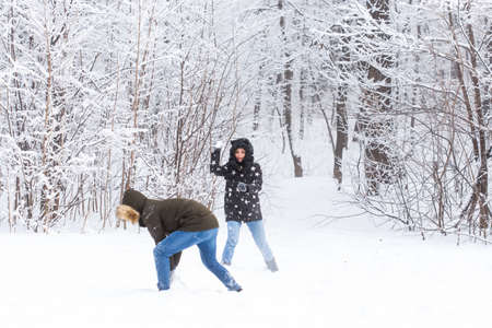 Lifestyle, season and leisure concept - Funny couple playing snowball in winter park