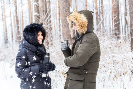 Season and walk concept - Happy couple drinking hot tea in winter forest