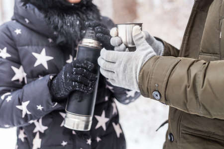 A woman pours a hot drink. Couple on a winter holiday Foto de archivo