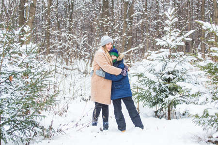 Fun and season concept - Happy mother and son having fun and playing with snow in winter forest