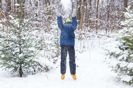 Cute young boy plays with snow, have fun, smiles. Teenager in winter park. Active lifestyle, winter activity, outdoor winter games, snowballs.