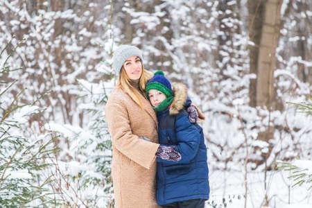 Portrait of happy mother with child son in winter outdoors. Snowy park. Single parent. Foto de archivo