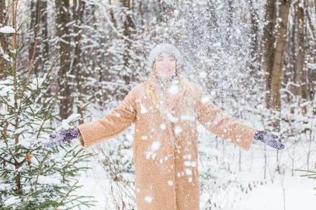Young woman throwing snow in the air at sunny winter day, she is happy and fun. Foto de archivo