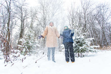 Parenting, fun and season concept - Happy mother and son having fun and playing with snow in winter forest