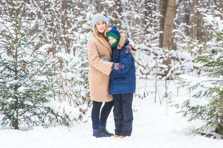 Portrait of happy mother with child son in winter outdoors. Snowy park. Single parent. Foto de archivo