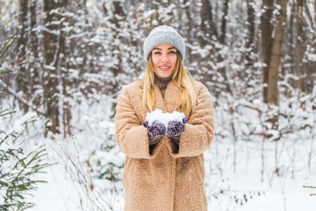 Close up of woman holding snow in hands, winter concept.