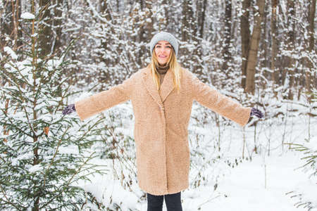 Attractive young woman in winter time outdoor. Snow, holidays and season concept.