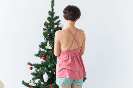 Back view of young woman decorating christmas tree. Holidays concept. Copy space.