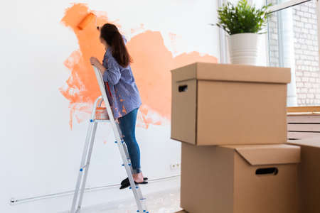 Renovation, redecoration and repair concept - Cheerful woman painting wall in new home. Foto de archivo
