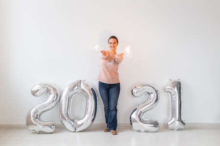 New Year celebration and party concept - Happy young woman with sparklers near silver 2021 balloons on white background.
