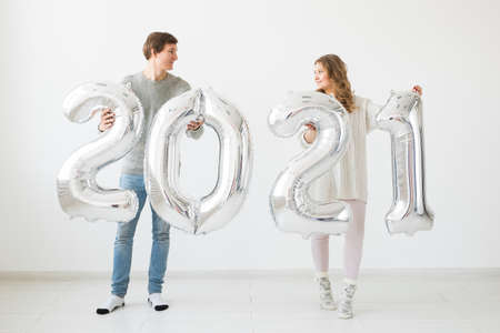 Holidays, festive and party concept - Happy loving couple holds silver 2021 balloons on white background. New Year celebration. Foto de archivo