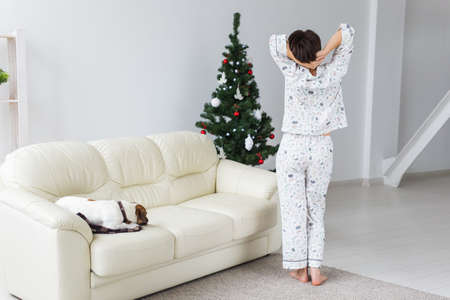 Happy young woman wearing pajama with lovely dog in living room. Holidays concept.