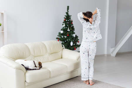 Pretty woman wearing pajama in living room with christmas tree. Holidays concept.