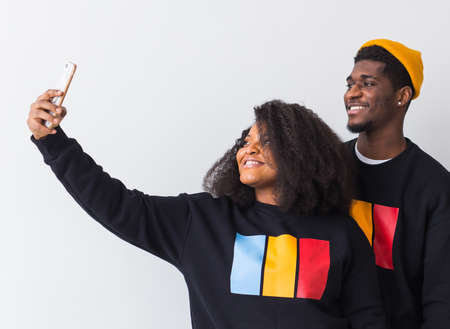 Friendship and fun concept - Group of friends afro american men and woman taking selfie in studio on white background.