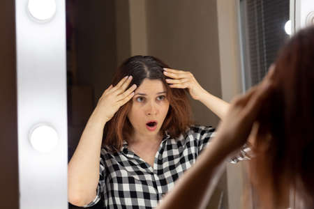 Horrified young woman looking in mirror staring open mouthed at the first grey hair on her scalp, a first sign of ageing.