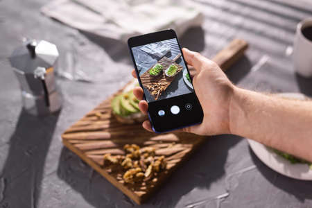 Hands take pictures on smartphone of two beautiful healthy sour cream and avocado sandwiches lying on board on the table. Social media and food concept 版權商用圖片