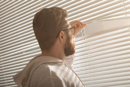 Rear view of young man with beard peeks through hole in the window blinds and looks out into the street. Surveillance and curiosity concept
