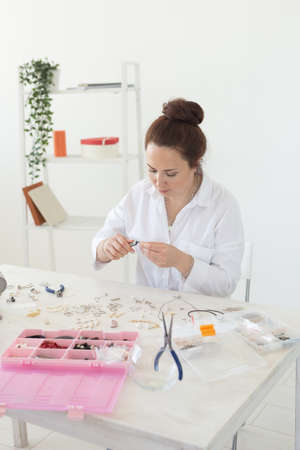 Beautiful young enthusiastic caucasian woman making beautiful unique costume jewelry while sitting at her work table. Concept of hobby and favorite work 版權商用圖片