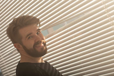 Young man with beard peeks through hole in the window blinds and looks out into the street. Surveillance and curiosity concept 版權商用圖片