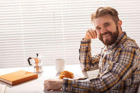 Pensive young bearded male businessman drinking cup of coffee on background of blinds. Concept of pleasant morning or lunch break.