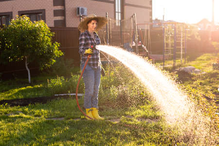 Happy woman gardener in work clothes watering the beds in her vegetable garden on sunny warm summer day. Concept of working in vegetable garden on your farm 版權商用圖片