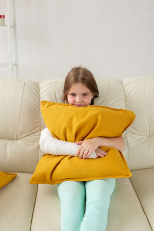Child with a cast on a broken wrist or arm sitting on a couch. Recovery and disease concept.