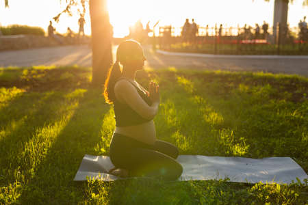Side view of young woman expecting baby in black suit stands on rug barefoot and meditates on warm sunny summer day. Concept of sports and meditation activities