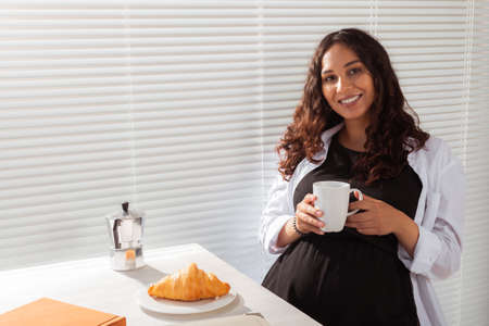 Joyful pregnant young beautiful woman looks at camera during her morning breakfast with coffee and croissants. Concept of good morning and waiting for meeting with a baby. Copyspace 版權商用圖片