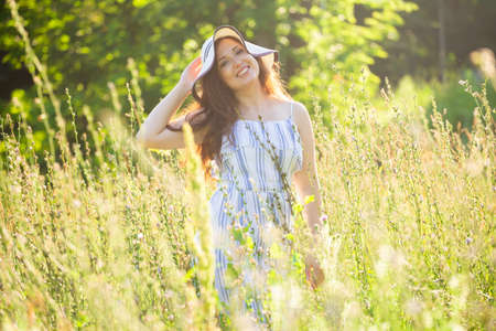 Young woman walking among wildflowers on sunny summer day. Concept of the joy of communicating with summer nature 版權商用圖片