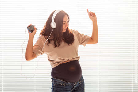 Curly-haired brunette pacified pregnant woman listens to pleasant classical music using smartphone and headphones. Concept of a soothing mood before meeting baby. 版權商用圖片