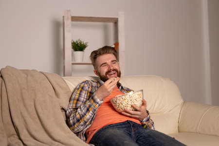 Bearded man watching film or sport games TV eating popcorn in house at night. Cinema, championship and fan concept.