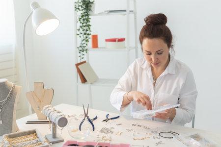 Professional jewelry designer making handmade jewelry in studio workshop. Fashion, creativity and handmade concept