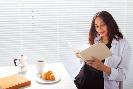 Side view of happy pregnant woman reading book while having morning breakfast with coffee and croissants on background of blinds. Good morning concept and pleasant lunch break