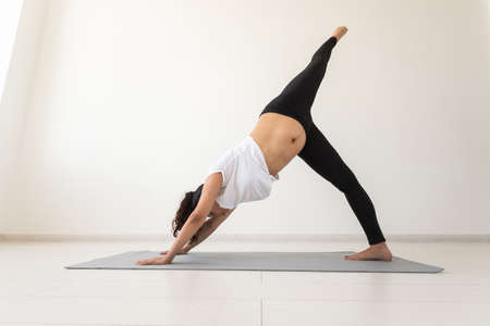 Young flexible pregnant woman doing gymnastics on rug on the floor on white background. The concept of preparing the body for easy childbirth