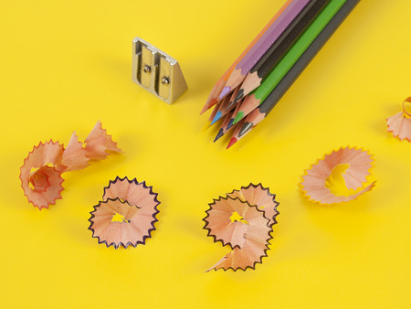 Some colored pencils of different colors and a pencil sharpener and pencil shavings on the yellow