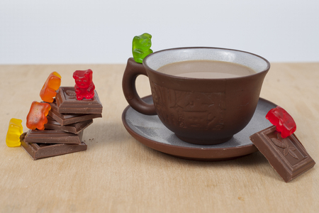 Chocolate and cup of coffee espresso on wood background with marmalade bears