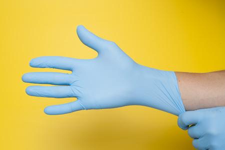 Doktor, der schützende blaue Handschuhe anzieht, die auf gelbem Hintergrund lokalisiert werden