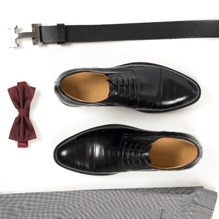Close up of modern man accessories. Bordeaux bow tie, leather shoes, belt on white  background. Set for formal style of wearing isolated on white background.