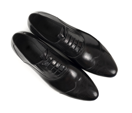 Top view of classic black leather shoes on white