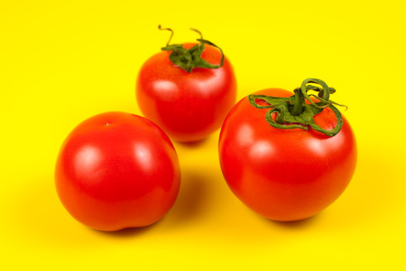 Fresh red tomato with green stem on yellow background