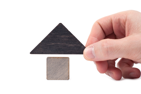 Wooden house toy blocks isolated white background, little wooden home with hand. The concept of buying and selling real estate, rental housing, building. Affordable housing, investment and construction.