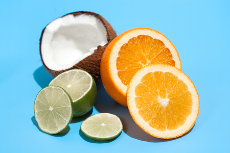 Fresh juicy orange, coconut and green lime isolated on blue background. Concept of Healthy eating and dieting. Travel and holiday concept