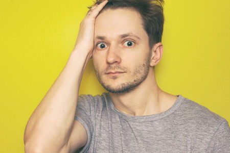 Shocked man looking at camera. Human emotions, facial expression concept. Yellow background