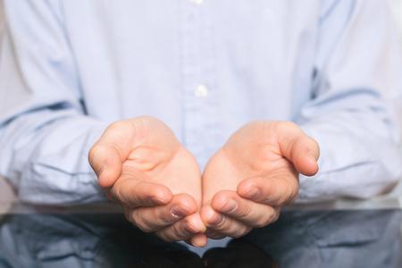 open handen van man teken van bedelen. man in shirt met iets denkbeeldigs op zijn handpalmen Stockfoto