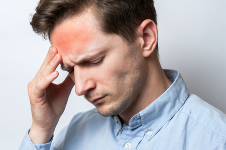 close up of tired young man suffering from headache on white background