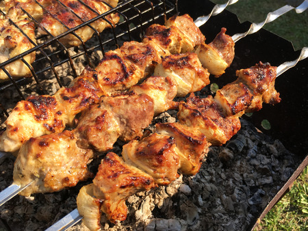 grill on the coals with smoke, barbecue. Pieces of chicken meat grilled on the grill. Stock Photo