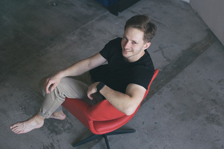 Portrait of a young beautiful man sitting on a red chair and looking into the camera.