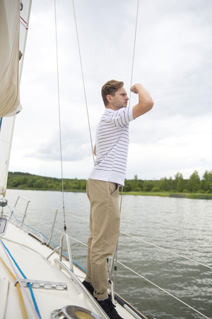 Handsome young man standing on yacht