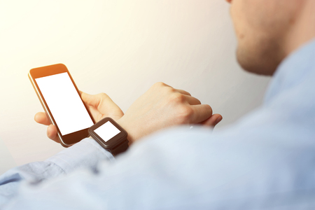 Side view, close-up of a smartphone with a blank screen and a smart watch on a male hand. Man using gadget. Reklamní fotografie
