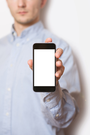 Portrait of casual men showing blank telephone screen while standing of white background Imagens